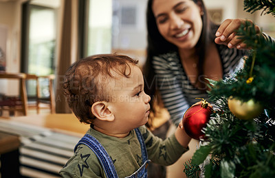 Buy stock photo Cropped shot of an adorable little girl and her mother decorating their Christmas tree for the festive season