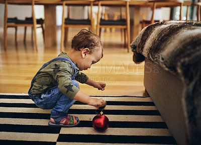 Buy stock photo Full length shot of an adorable little girl playing with the Christmas decorations at home