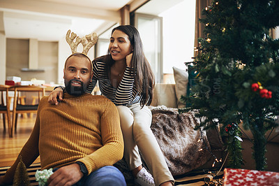 Buy stock photo Cropped shot of an affectionate young couple chilling in their living room on Christmas morning