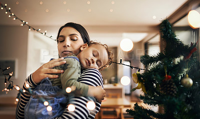 Buy stock photo Cropped shot of an attractive young woman carrying her sleeping daughter through the living room on Christmas morning
