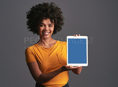 Buy stock photo Shot of a beautiful young woman holding up a digital tablet against a grey background