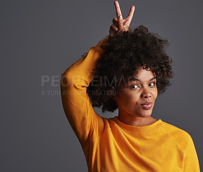 Buy stock photo Shot of a beautiful young woman holding the peace sign behind her head