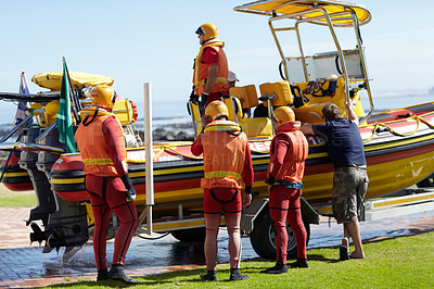 Buy stock photo Full length shot of a group of lifeguards preparing to go out to sea on a rescue mission