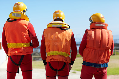 Buy stock photo Rearview shot of three unrecognizable lifeguards keeping their eyes on the ocean and the horizon