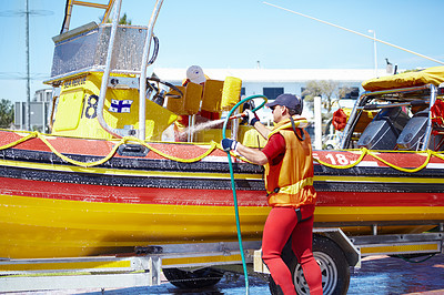 Buy stock photo Cropped shot of a handsome young male lifeguard cleaning the boat after a rescue mission