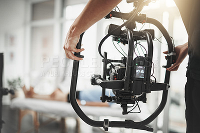 Buy stock photo Behind the scenes shot of an unrecognizable camera operator shooting a scene with a state of the art camera inside of a studio during the day