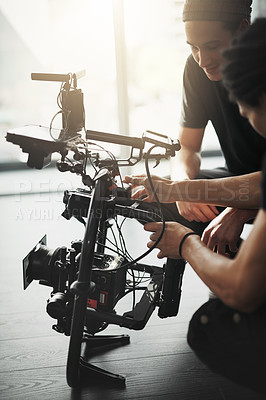 Buy stock photo Behind the scenes shot of two young camera operators shooting a scene with a state of the art camera inside of a studio during the day