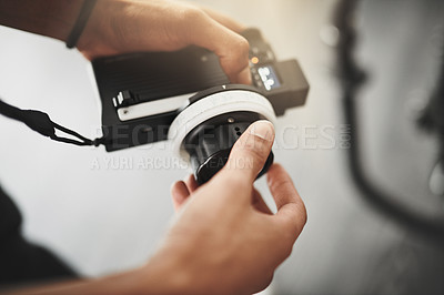 Buy stock photo Behind the scenes over the shoulder shot of an unrecognizable person operating state of the art video camera equipment inside of a studio