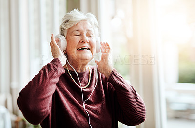 Buy stock photo Shot of happy senior woman listening to music with headphones at a retirement home