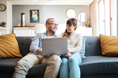 Buy stock photo Cropped shot of a young couple using a laptop while relaxing on the sofa in the living room at home