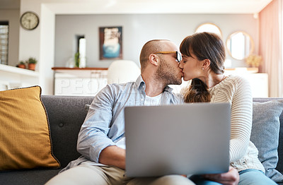 Buy stock photo Cropped shot of a young couple being affectionate while relaxing on the sofa in the living room at home