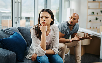 Buy stock photo Shot of a young woman looking upset after a fight with her partner at home