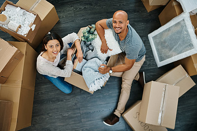 Buy stock photo Portrait of a young couple sorting boxes while moving house