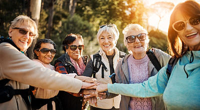 Buy stock photo Cropped portrait of a group of happy senior women standing with their hands in huddle during a hike in the great outdoors