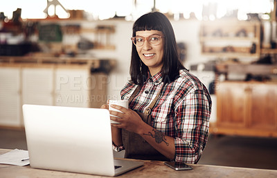 Buy stock photo Cropped portrait of an attractive young woman working on her laptop while sitting in her creative workshop