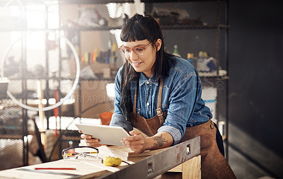 Buy stock photo Cropped shot of an attractive young woman working on her tablet while standing in her creative workshop