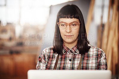 Buy stock photo Cropped shot of an attractive young woman working on her laptop while sitting in her creative workshop
