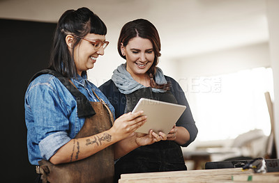Buy stock photo Cropped shot of two attractive young creative female artisans working on a tablet in their workshop