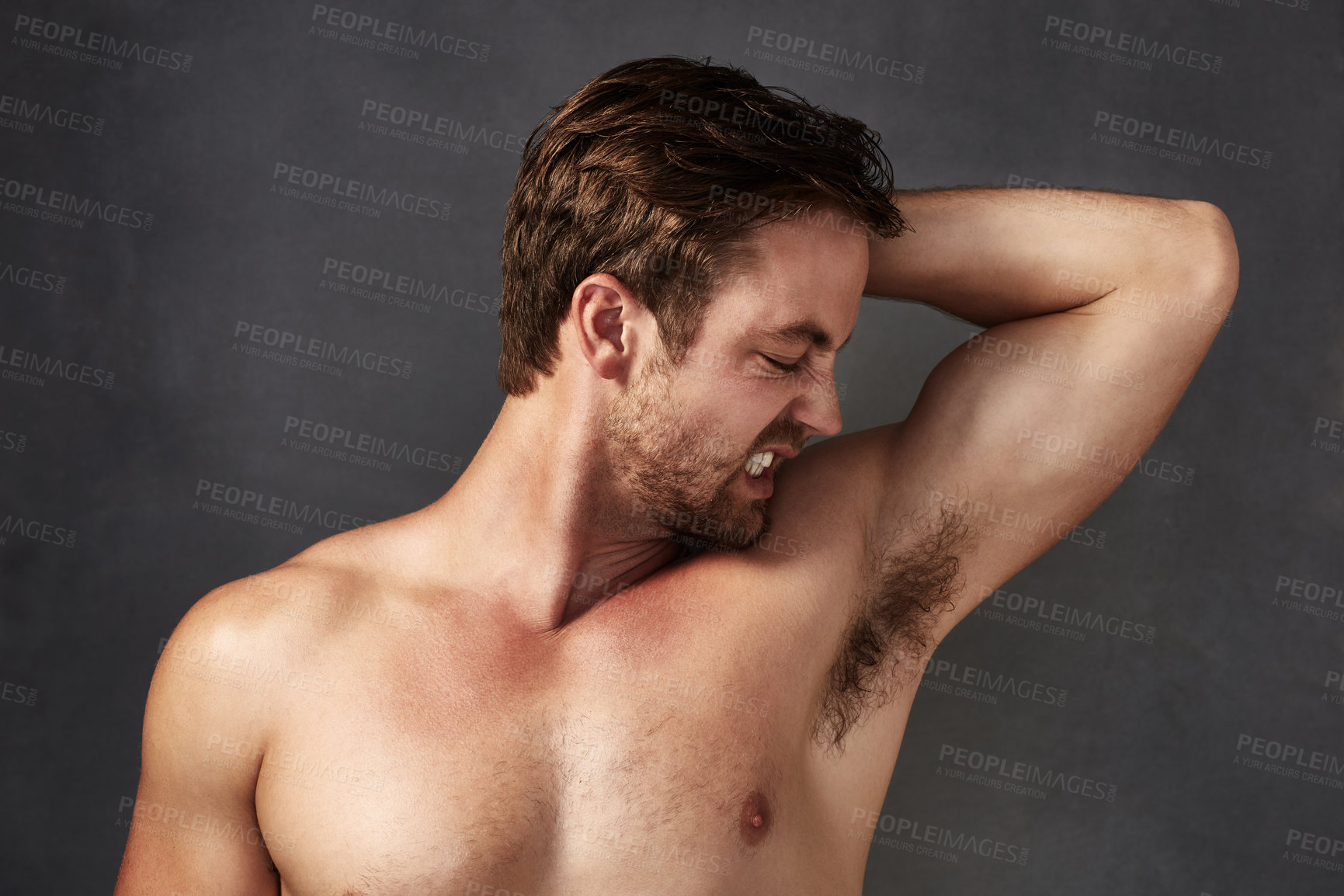 Buy stock photo Cropped shot of a handsome young man smelling his stinky armpits