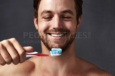 Buy stock photo Cropped shot of a handsome young man brushing his teeth against a grey background