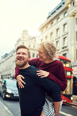 Buy stock photo Shot of a happy young couple enjoying a piggyback ride in the city