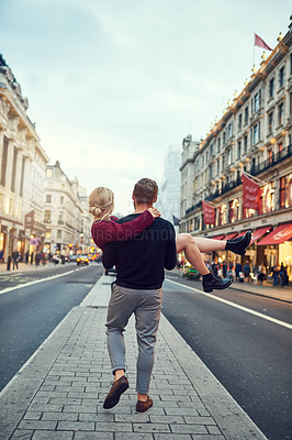 Buy stock photo Shot of a young man carrying his girlfriend through the city streets