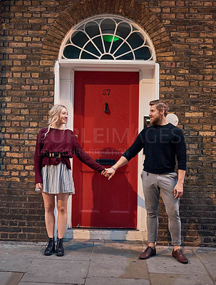Buy stock photo Shot of an affectionate young couple holding hands in the city