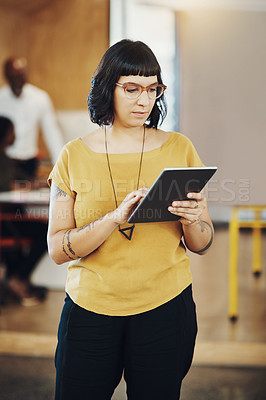 Buy stock photo Cropped shot of a businesswoman using a digital tablet while at the office