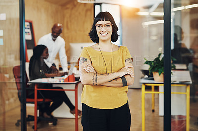 Buy stock photo Shot of a creative businesswoman standing in her office with colleagues blurred in the background