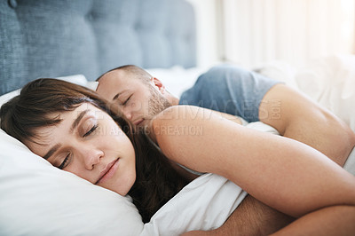 Buy stock photo Shot of a young couple sleeping peacefully in bed at home