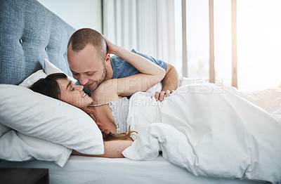 Buy stock photo Shot of a young couple sharing a romantic moment in bed