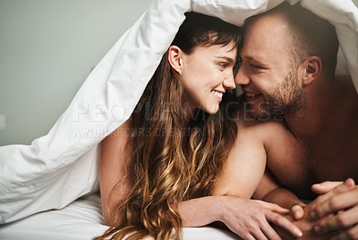 Buy stock photo Shot of a young couple sharing a romantic moment under a blanket in bed