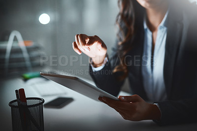 Buy stock photo Cropped shot of a  businesswoman using a digital tablet while working late in a modern office