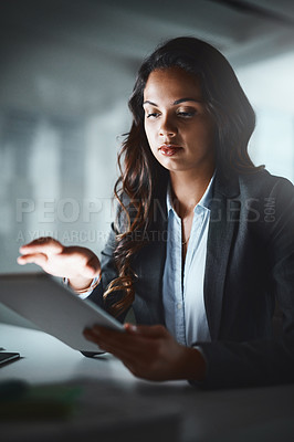 Buy stock photo Shot of a young businesswoman using a digital tablet while working late in a modern office