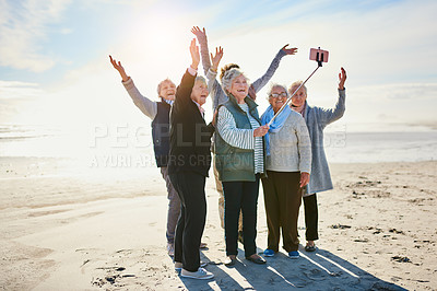 Buy stock photo Shot of a group of happy senior women taking selfies at the beach