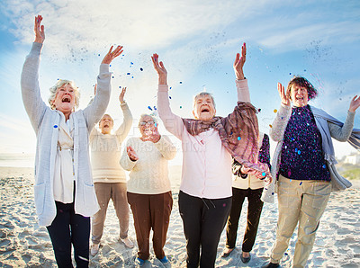 Buy stock photo Shot of a group of happy senior women throwing confetti in the air at the beach