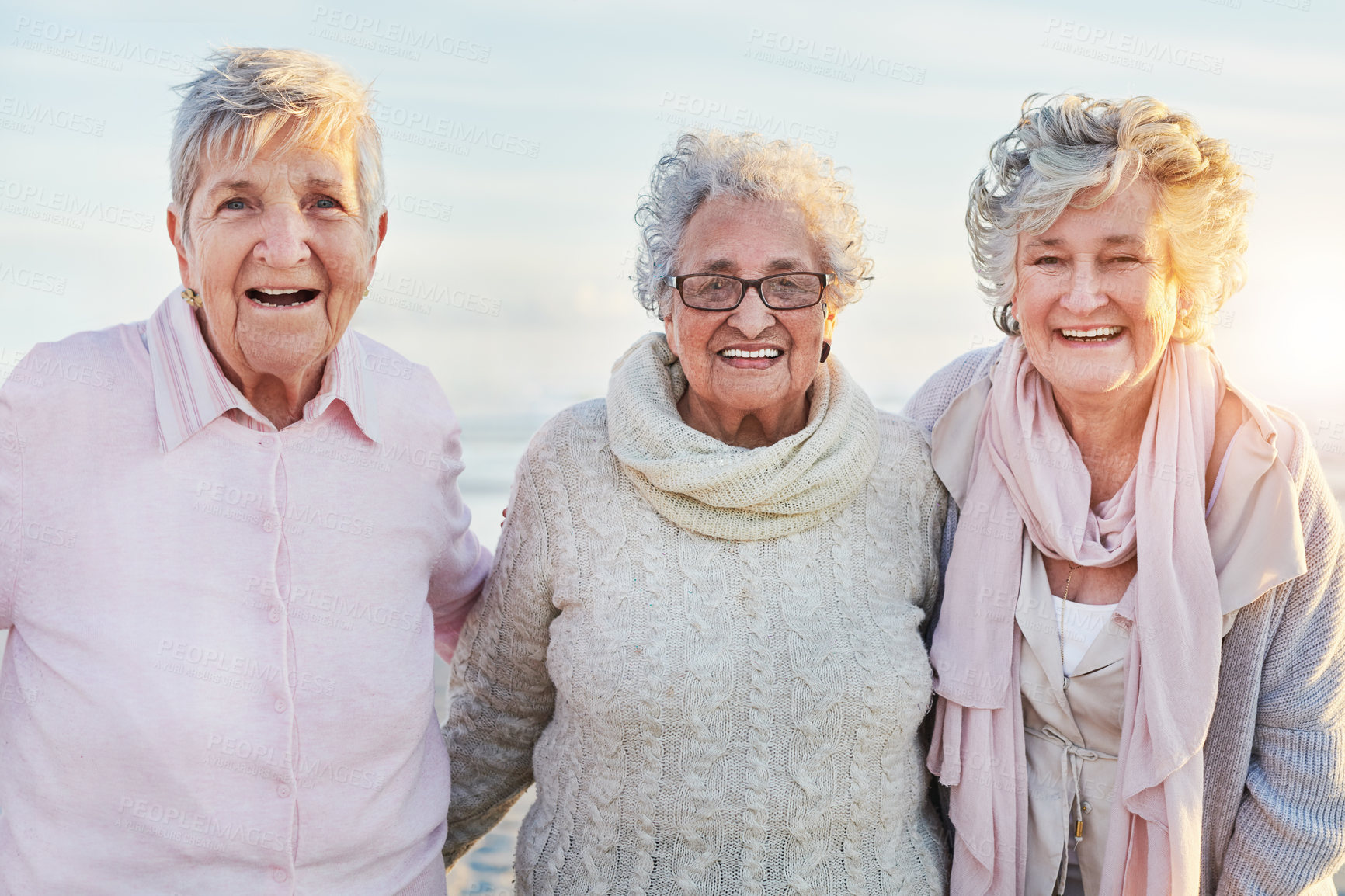 Buy stock photo Portrait of a group of happy senior women enjoying a day at the beach
