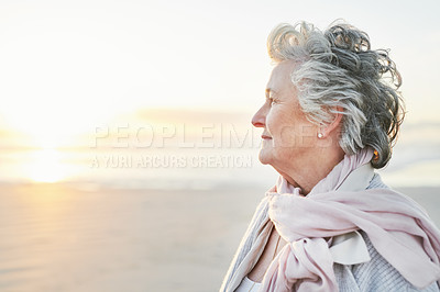 Buy stock photo Shot of a senior woman looking thoughtful at the beach