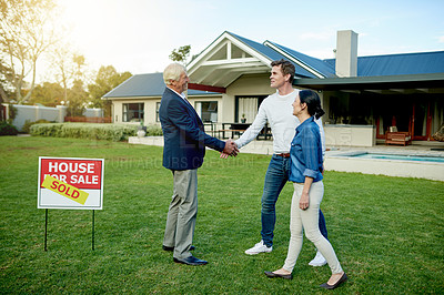 Buy stock photo Shot of a couple standing outside of their new home with their real estate agent