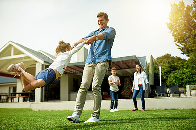 Buy stock photo Shot of a man spinning his daughter around in their backyard