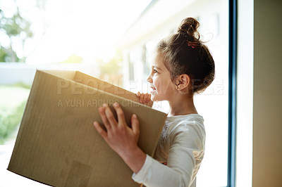 Buy stock photo Cropped shot of a little girl carrying a box in her new house