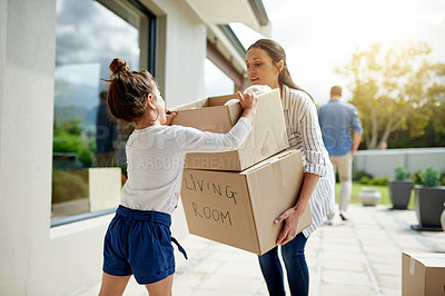 Buy stock photo Shot of a little girl helping her mom to carry boxed into their new home