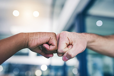 Buy stock photo Cropped shot of two people giving each other a fist bump in a modern office