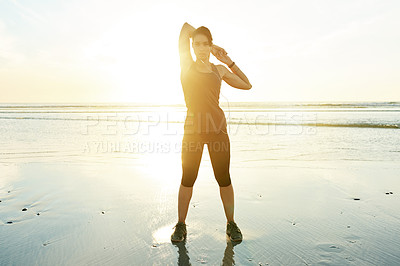 Buy stock photo Full length shot of an attractive and athletic young woman working out on the beach