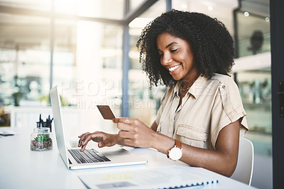 Buy stock photo Shot of a young businesswoman using a credit card and laptop in a modern office