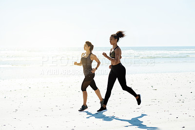 Buy stock photo Full length shot of two attractive and athletic young women out for a run on the beach