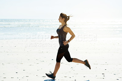 Buy stock photo Full length shot of an attractive and athletic young woman out for a run on the beach
