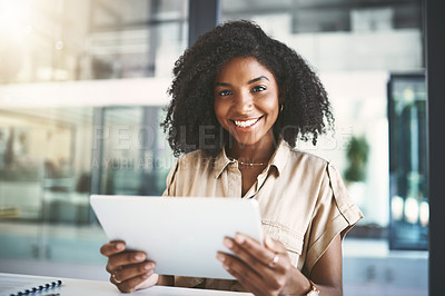 Buy stock photo Portrait of a young businesswoman using a digital tablet at her desk in a modern office
