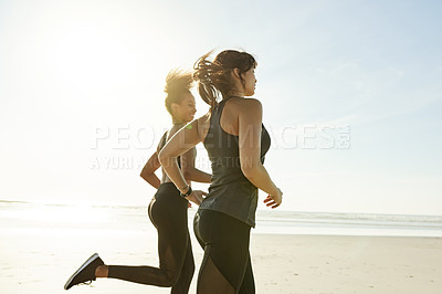 Buy stock photo Rearview shot of two attractive and athletic young women out for a run on the beach