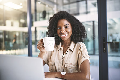 Buy stock photo Portrait of a young businesswoman using a laptop and drinking coffee at her desk in a modern office